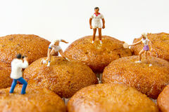 Tiny toys play tennis on the banana cake.Food background Royalty Free Stock Image