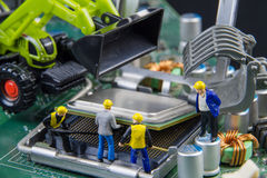 Tiny toys team of engineers repairing circuit mother board compu Royalty Free Stock Images