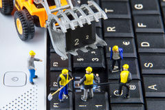 Tiny toys team of engineers repairing keyboard computer laptop.Computer equipment.Computer repair concept royalty free stock photography