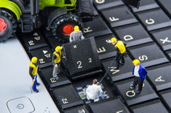 Tiny toys team of engineers repairing keyboard computer laptop.Computer equipment.Computer repair concept royalty free stock image