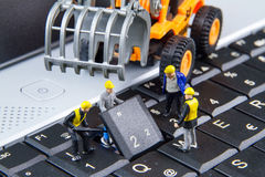 Tiny toys team of engineers repairing keyboard computer laptop.Computer equipment.Computer repair concept stock images