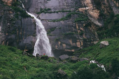 Tiny traveler figure near the Yogini waterfall in Indian Himalay Stock Photography