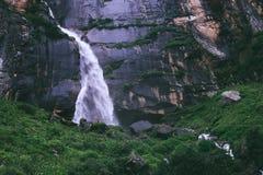 Tiny traveler figure near the Yogini waterfall in Indian Himalay Royalty Free Stock Photos