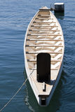 Tiny wooden boat on the bright blue sea Stock Photos