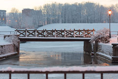 Tiny wooden bridge over the frozen canal. Klaipeda, Lithuania Royalty Free Stock Photo