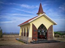 Tiny yellow chapel with steeple at ocean side in Puerto Rico. Little chapel with large doors open to welcome visitors at edge of ocean, under blue clouded sky stock photo