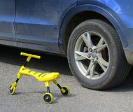 Big wheels, small wheels, young and old. A tiny yellow tricycle alongside a car`s mag wheel, transport for the old and the young royalty free stock image