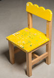 The tiny yellow wooden chair. On the floor Stock Images