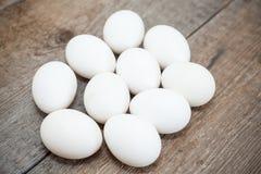 Tio fega vita ägg är på trägolv Royaltyfri Fotografi