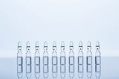 Tio genomskinliga ampuller med flytande inom Arkivfoto