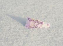Tio indonesiska rupiahs för tusentals från snön Begrepp Arkivfoto