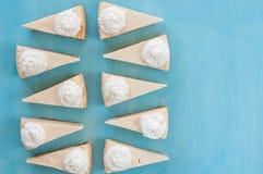 Tio stycken av ostkaka på en blå bakgrund, bästa sikt, som sötsaken, gottegris, royaltyfri bild