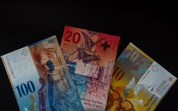 Tio, tjugo och hundra schweizisk franc schweizisk valuta på svart bakgrund royaltyfri fotografi