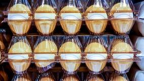 Tio vita ägg i brun plast- packe på marknad bordlägger fotografering för bildbyråer