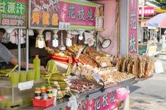 Tioarmad bläckfisk- och bambufruktsaftförsäljare på Danshui som shoppar område Arkivbilder