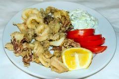 Tioarmad bläckfisk ringer stekt Räka med limefrukt på den svarta plattan crete greece Royaltyfri Bild