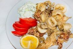 Tioarmad bläckfisk ringer stekt Räka med limefrukt på den svarta plattan crete greece Arkivfoton