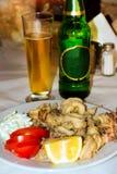 Tioarmad bläckfisk ringer stekt Räka med limefrukt på den svarta plattan crete greece Arkivfoto