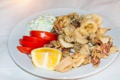 Tioarmad bläckfisk ringer stekt Räka med limefrukt på den svarta plattan crete greece Fotografering för Bildbyråer