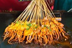 Tioarmade bläckfiskar grillar med den högg av salladslöken Royaltyfria Foton