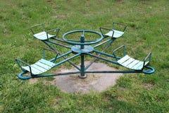 Tiovivo público al aire libre del metal del vintage del equipo del patio con el marco aherrumbrado y los asientos dilapidados imagen de archivo libre de regalías