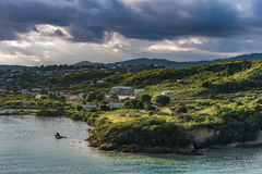 Tip of Antigua Island at sunrise with stormy sky. View from the ocean of the tip of Antigua Island at sunrise with stormy sky Stock Images