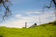 Tip of Barn over Green Field Royalty Free Stock Photography