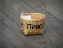 Tip box. On the wooden floor waiting to be filled with money, closeup shot stock image