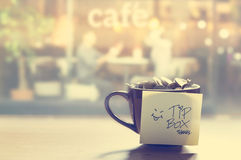Tip box, coin in the coffee cup in cafe front of mirror, Vintage color and soft Royalty Free Stock Photography