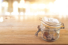 Tip box, coin in the glass jar in cafe front of mirror Stock Images