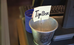 Tip box on counter. Tin tip box with yellow paper on counter Stock Images