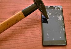 The tip of the hammer hit the screen of the smartphone. A network of cracks on the glass draws a spider`s web. The screen is irretrievably broken royalty free stock photography