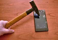 The tip of the hammer hit the screen of the smartphone. A network of cracks on the glass draws a spider`s web. The screen is irretrievably broken stock image