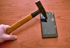 The tip of the hammer hit the screen of the smartphone. A network of cracks on the glass draws a spider`s web. The screen is irretrievably broken stock photography