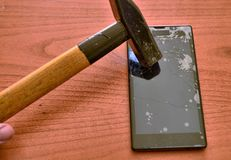 The tip of the hammer hit the screen of the smartphone. A network of cracks on the glass draws a spider`s web. The screen is irretrievably broken stock photo