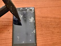 The tip of the hammer hit the screen of the smartphone. A network of cracks on the glass draws a spider`s web. The screen is irretrievably broken royalty free stock photos