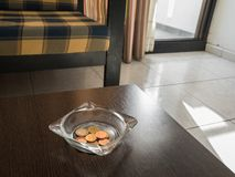 Tips in the ashtray on a hotel table. Tip for the hotel maid in the ashtray on the table in a hotel room Royalty Free Stock Image