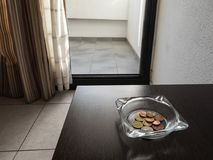 Tips in the ashtray on a hotel table. Tip for the hotel maid in the ashtray on the table in a hotel room Stock Images