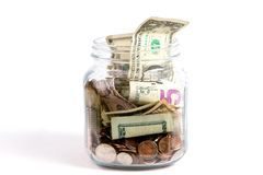 Tip Jar. US dollars and coins fill a glass tip jar with money royalty free stock photo