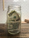 Tip jar full of dollar bills Royalty Free Stock Images
