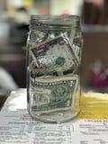 Tip jar full of dollar bills Royalty Free Stock Photos