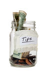 Tip jar with money. A tip jar with coins and bills Stock Photos