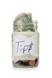 Tip jar with money. A tip jar with coins and bills Stock Images