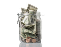 Tip Jar Overflowing. A tip jar or jar for savings filled over the top with American coins and bills stock photos