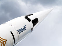 Tip of large US Army surplus missile. Nicknamed SERGEANT npointed toward cloudy, grey sky stock image