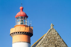 Tip of a a lighthouse and a chapel Royalty Free Stock Images