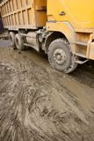 Tip lorry moving on a muddy road Stock Images