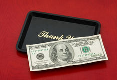Tip Money. A one hundred dollar bill on a black tray on a wood background, tip money stock image
