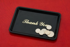 Tip Money. Silver coins on a black tray on a wood background, tip money stock photography