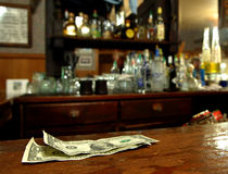 Tip Money On The Bar. A Couple of Dollars Awaits The Bartender in a Rustic Bar Royalty Free Stock Image
